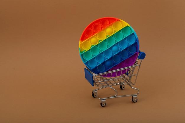 Jouet pop it fidget tendance dans un chariot d'épicerie nouveau jouet pop it anti-stress populaire de forme ronde