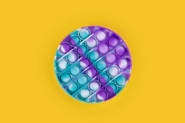 Jouet popit rond de couleur pastel antistress pour enfants et adultes sur fond jaune. jouet anti-stress sensoriel flexible pop it forme ronde, espace de copie