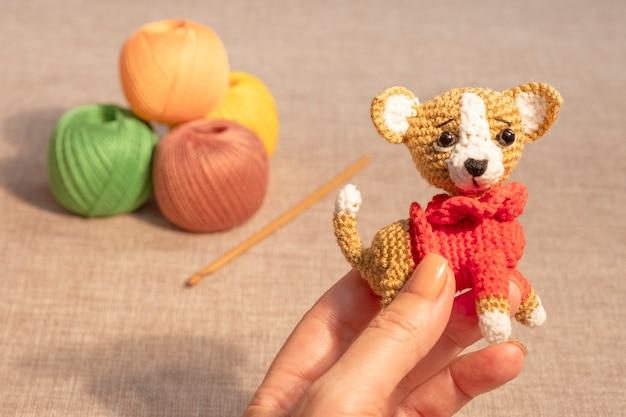 Un jouet pour chiot dans la main d'une femme sur fond de boules à tricoter. hobbies jouets au crochet.