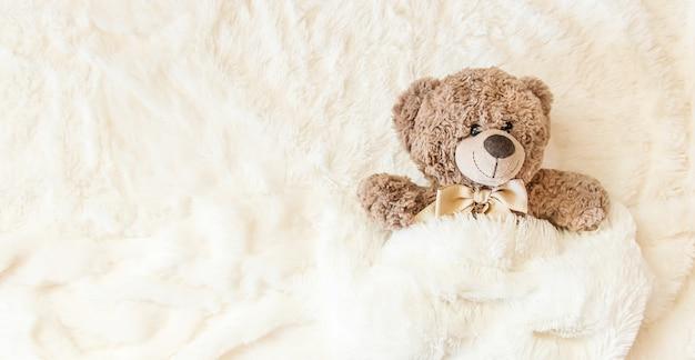 Le jouet pour enfants dort sous la couverture. espace de copie. mise au point sélective.