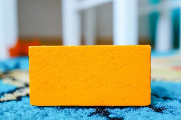 Jouet rectangulaire orange pour enfants posé sur une surface multicolore