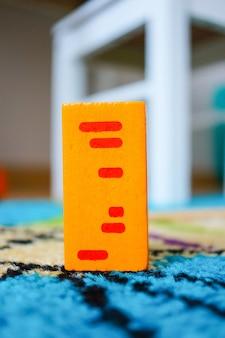Jouet rectangulaire pour enfants posé sur une surface multicolore