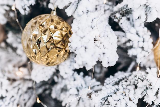 Jouet rond en or sur le sapin de noël. concept de noël et du nouvel an