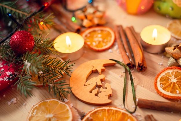 Jouet de sapin de noël en bois avec illustration biblique allongé sur la table parmi une décoration festive lumineuse