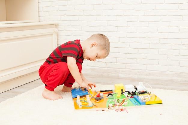 Jouet sensoriel pour enfants bricolage fait à la main, un garçon de trois ans joue avec une planche occupée