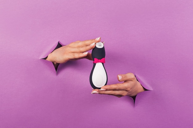 Un jouet sexuel en silicone pingouin noir et blanc sur fond rose dans les mains des femmes jouet érotique pour le plaisir