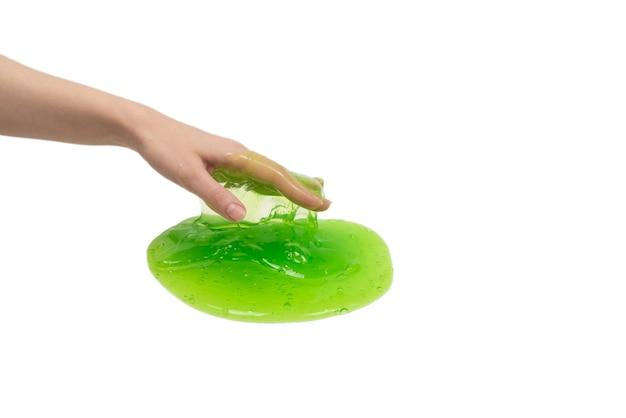 Jouet de slime vert dans la main de la femme isolé sur fond blanc.