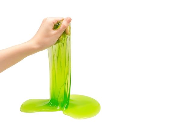 Jouet de slime vert en main de femme isolé sur blanc.