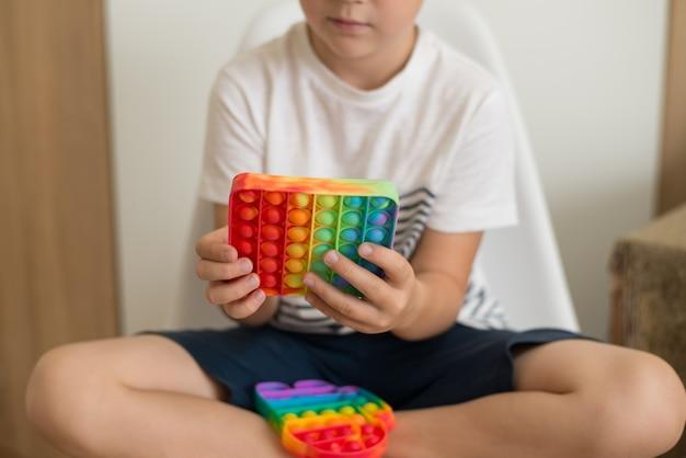 Jouet tactile antistress coloré populaire fidget push pop it dans les mains d'un jouet popit enfant