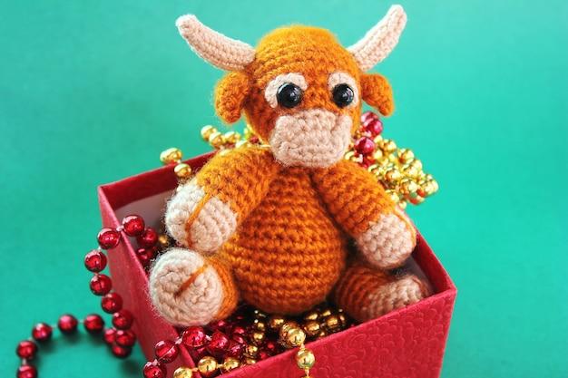 Un jouet taureau tricoté est dans une boîte rouge avec des perles de noël sur un fond vert
