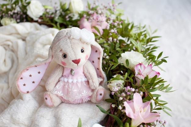Jouet teddy rabbit sur un plaid tricoté. beau jouet élégant fait à la main avec des fleurs