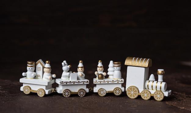 Jouet de train blanc en bois sur brun foncé.