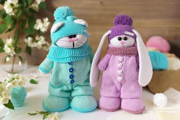Jouet tricoté à la main sur fond de bois. deux animaux un chat, un lapin.