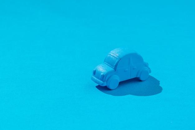 Jouet voiture bleue sur un bleu clair. le concept de vente et d'achat de voitures.