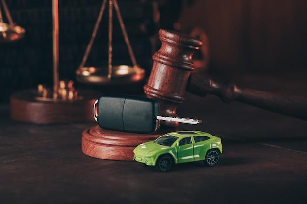 Jouet de voiture et marteau en bois. concept de vente d'une voiture aux enchères ou d'une sentence d'accident