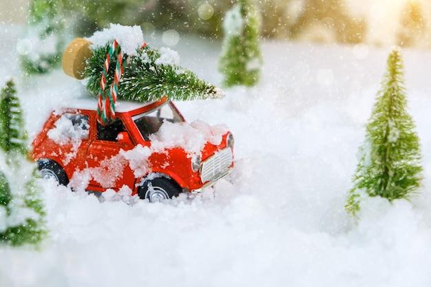 Jouet de voiture vintage rouge transportant un arbre de noël à la maison à travers une merveille d'hiver enneigé. profondeur de champ extrêmement faible avec mise au point sélective sur le véhicule