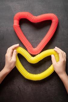 Jouets anti-stress sensoriels à tube pop dans les mains des enfants. de petits enfants heureux jouent avec un jouet poptube sur une table noire. tout-petits tenant et jouant des tubes pop couleur vive rouge et jaune, tendance 2021 année