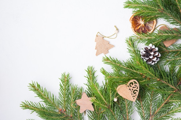 Jouets d'arbre de noël et branches d'épinette naturelles sur fond blanc vue de dessus copie place, jouets d'arbre de noël écologiques faits maison sur des branches d'épinette fraîches
