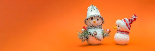Jouets de bonhomme de neige isolés sur la bannière de fond orange