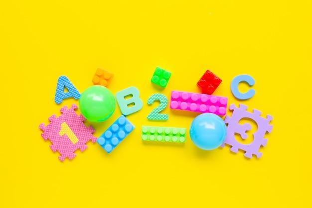 Jouets colorés pour enfants sur jaune.