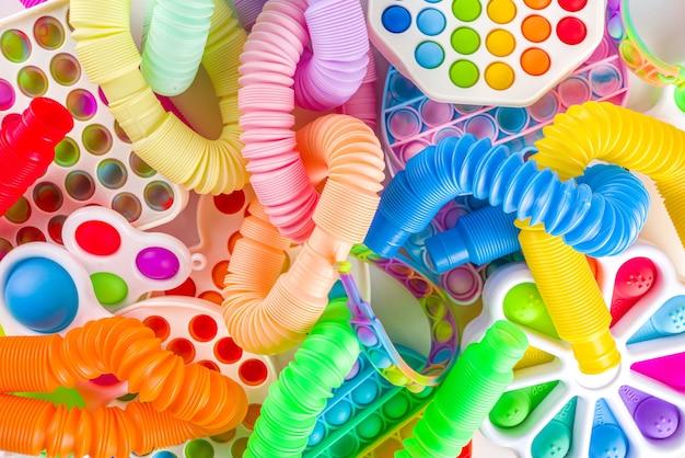 Jouets à doigts pour enfants à la mode modernes, concept de relaxation - ensemble de différents pop-it lumineux, simples à fossettes, spongieux, tubes pop, sur fond blanc, espace de copie vue de dessus
