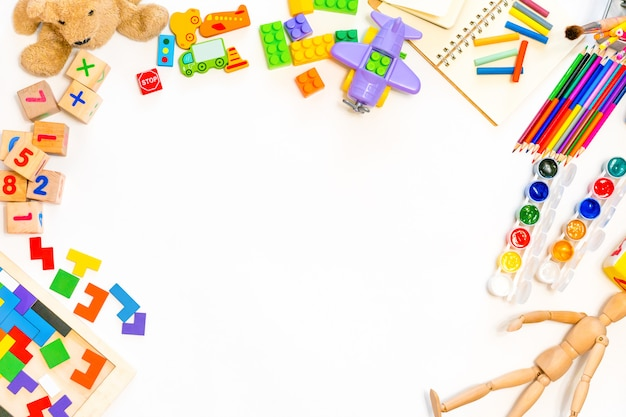 Jouets éducatifs colorés et fournitures scolaires sur fond blanc. cadre de blocs de bois pliants, voitures, crayons, peintures. fond pour les classes préscolaires et maternelles ou artistiques. mise à plat espace copie