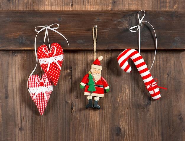 Jouets faits à la main en textile de décoration de noël suspendus au-dessus d'un fond en bois rustique. photo tonique de style rétro nostalgique