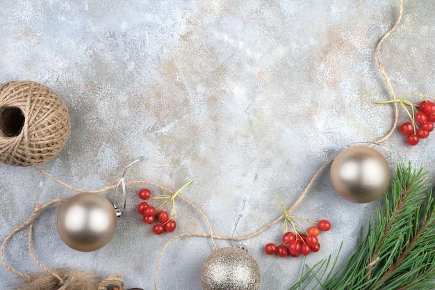 Jouets de noël avec des ballons et viburnum rouge sur une surface grise