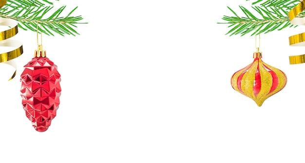 Jouets de noël bosse rouge et tourbillon d'or sur une branche d'épinette verte isolée sur blanc avec espace de copie.