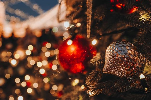Jouets de noël boules d'or rouge accrochées à l'arbre de noël avec un bokeh festif doré flou