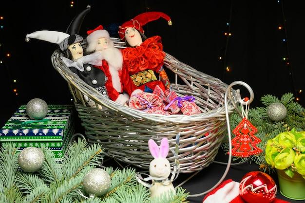 Jouets de noël dans un traîneau, cadeaux, balles et père noël. concept de noël et nouvel an sur fond noir.