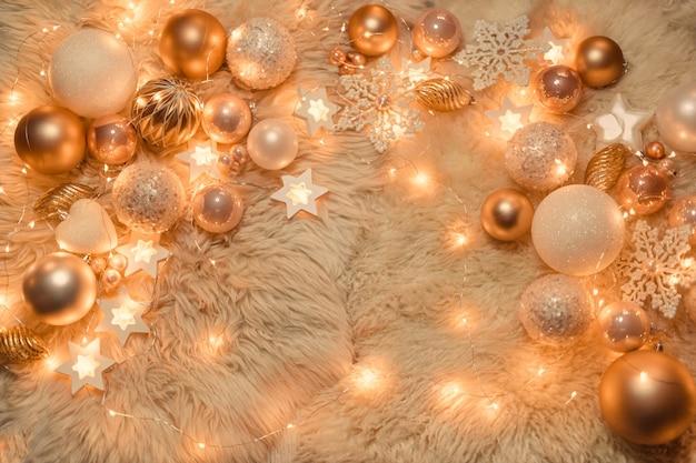 Jouets de noël dorés et roses au milieu des lumières allumées de guirlandes, mise à plat, vue de dessus, espace de copie.