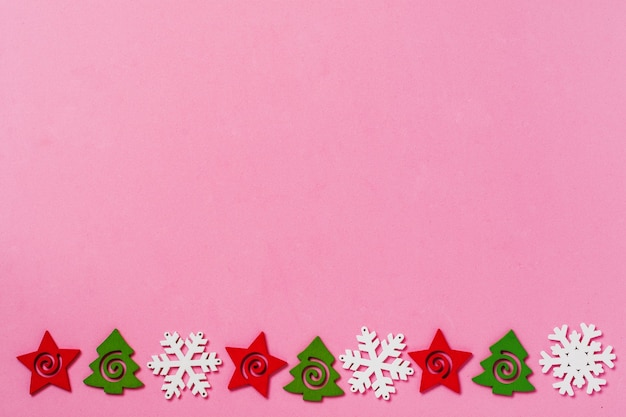 Jouets de noël et flocons de neige se trouvant sur un fond de surface rose. concept de nouvel an ou de noël. vue de dessus. faire face à l'espace