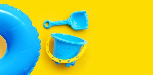 Jouets en plastique, anneau de piscine avec seau et pelle pour sable sur surface jaune.