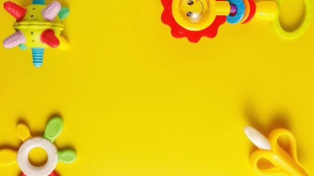 Jouets en plastique colorés et divers pour bébés sur fond jaune.