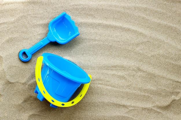 Jouets en plastique, pelle et seau sur le sable. concept de fond d'été