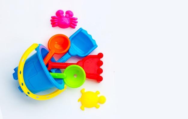 Jouets en plastique, pelles dans un seau pour le sable sur une surface blanche.
