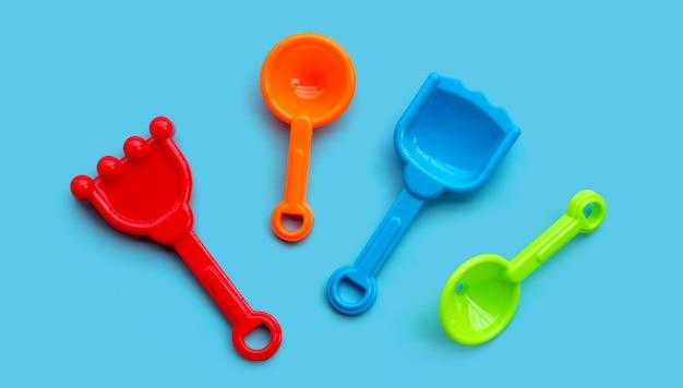 Jouets en plastique, pelles pour le sable sur fond bleu.
