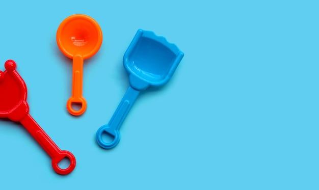 Jouets en plastique, pelles sur surface bleue.