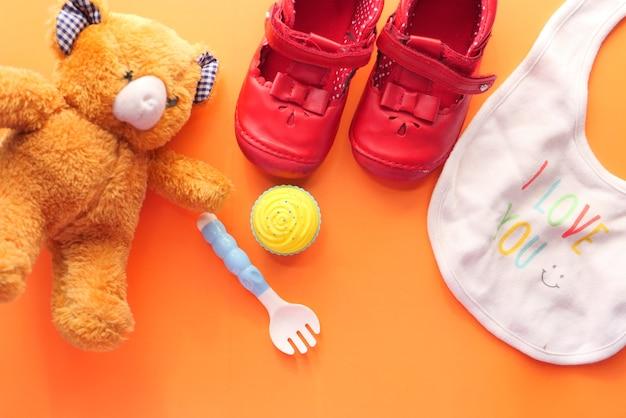 Jouets pour bébé nouveau-né avec ours en peluche et chaussure sur orange