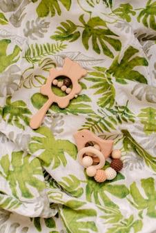 Jouets pour bébés sur tissu mousseline imprimé feuilles