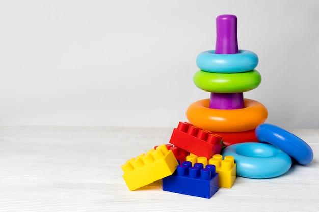 Jouets pour le développement de la motricité des enfants d'âge préscolaire sur un fond en bois clair avec une place pour le texte. pyramide brillante d'anneaux et de briques colorées.
