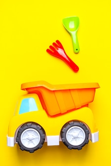 Jouets pour enfants colorés - camion et pelle, cuillère sur jaune