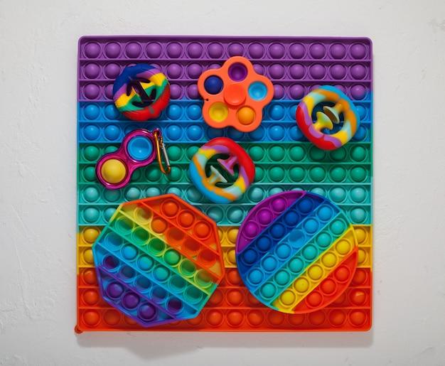 Jouets pour enfants colorés populaires (spinner, simple fossette, pop it et snapperz) vue de dessus.