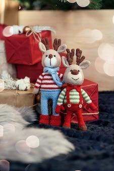 Jouets pour enfants. deux élégants cerfs amigurumi en pulls rayés, une écharpe et une cravate papillon se tiennent près des cadeaux de noël.