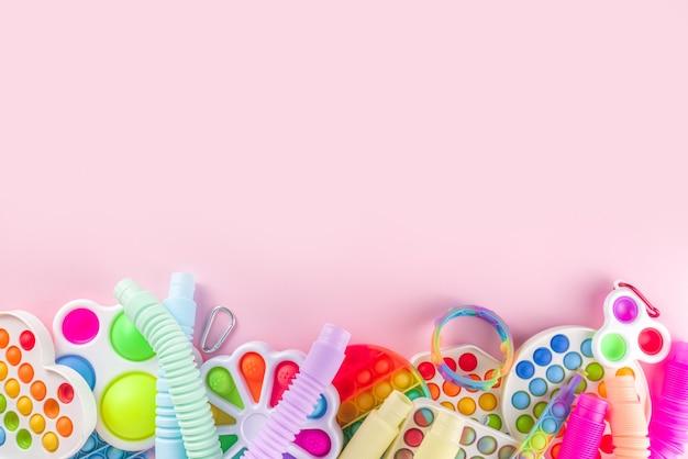 Jouets pour enfants à la mode moderne, concept de relaxation - ensemble de différents pop-it lumineux, simples à fossettes, visqueux, tubes pop, sur fond rose coloré, espace de copie vue de dessus