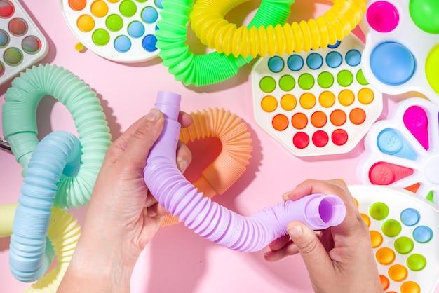 Jouets pour enfants à la mode et modernes, concept de relaxation - les mains de la femme jouent avec différents pop-it lumineux, simples à fossettes, spongieux, tubes pop, sur fond blanc, espace de copie vue de dessus