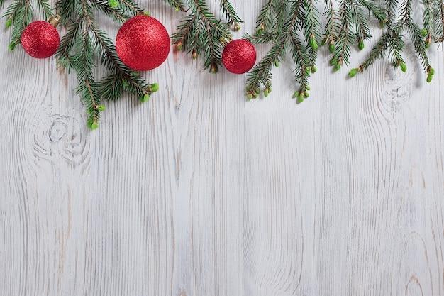 Jouets rouges de noël et branches d'épinette sur une table en bois