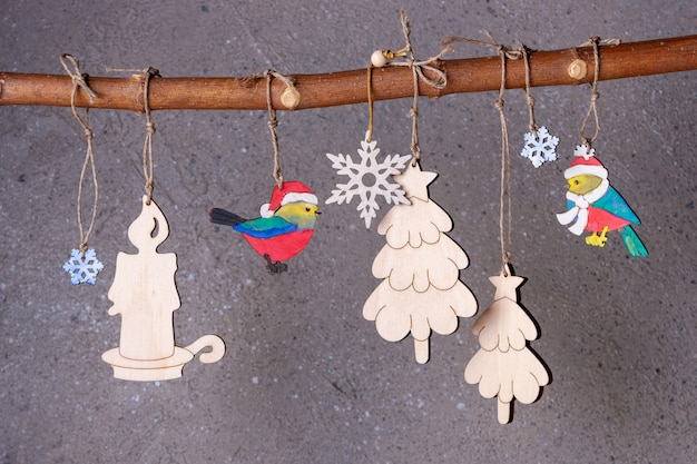 Des jouets de sapin de noël en bois peints à la main sont suspendus à une branche