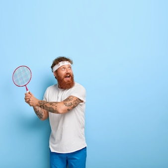 Joueur actif et joyeux concentré joyeusement sur la distance, tient la raquette et joue au badminton
